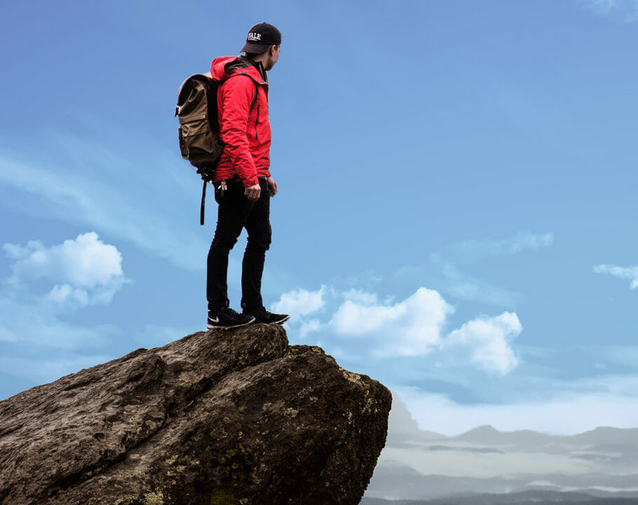 Young man stood on top of a mountain